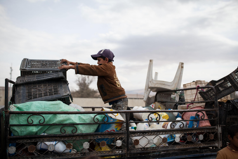 Un jeune enfant empile les déchets sur la camionnette