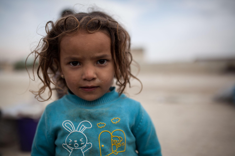 Une petite fille reste avec les autres enfants qui reviennent de la décharge municipale